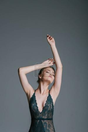 Photo for Sensual beautiful young girl with slim body posing in green lace bodysuit, isolated on grey - Royalty Free Image