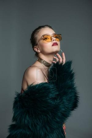 fashionable model in fur coat and sunglasses