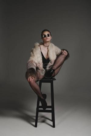 Photo for Seductive fashionable young girl in sunglasses, black sexy clothes and fur coat sitting on stool on grey - Royalty Free Image