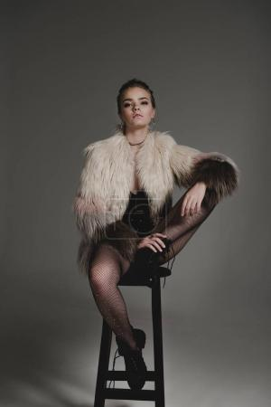Photo for Seductive fashionable young girl in black sexy clothes and fur coat sitting on stool on grey - Royalty Free Image
