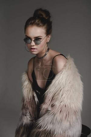 Girl in sunglasses and fur coat