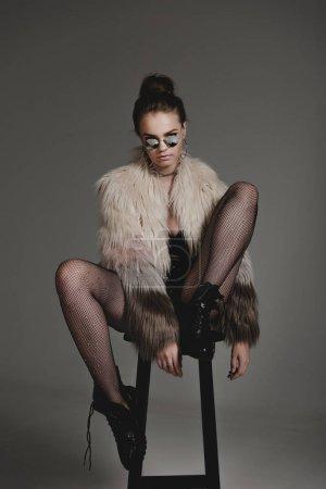 Photo pour Séduisante jeune fille élégante en lunettes de soleil, vêtements sexy noirs et manteau de fourrure, assis sur le tabouret sur fond gris - image libre de droit