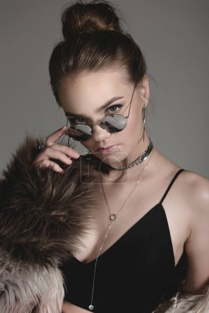 Photo for Attractive stylish young girl posing sunglasses, in black sexy clothes and fur coat on grey - Royalty Free Image