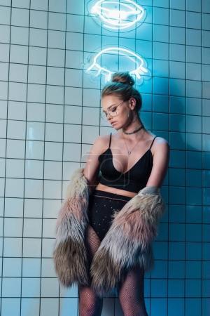 Photo pour Belle jeune femme à la mode posant dans des tenues sexy noirs et manteau de fourrure près d'enseignes au néon - image libre de droit