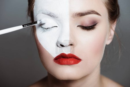 Girl applying bodyart on face