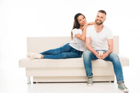 Photo for Young attractive couple sitting on couch, isolated on white - Royalty Free Image
