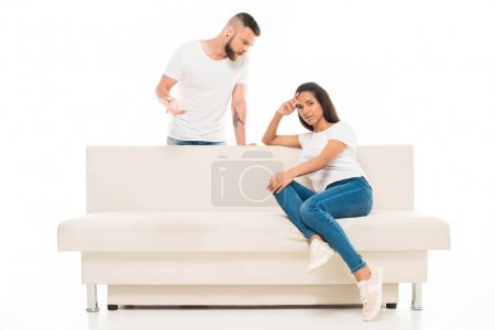 Photo for Young man talking with attractive woman sitting on couch, isolated on white - Royalty Free Image