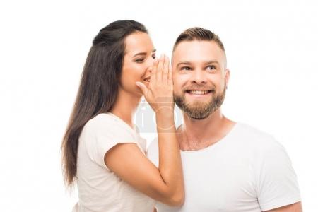 Young woman whispering to boyfriends ear