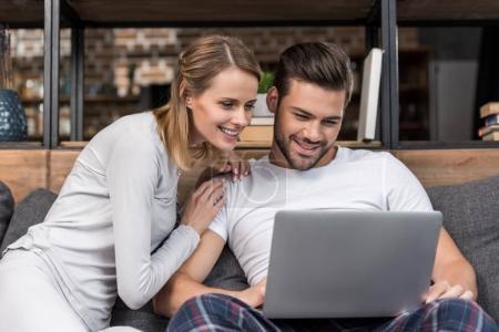 Photo pour Heureux jeune couple utilisant un ordinateur portable tout en étant assis sur le canapé à la maison - image libre de droit