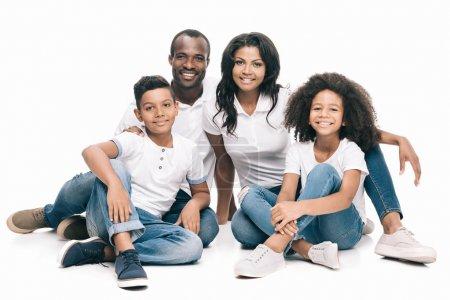 Photo pour Belle famille afro-américaine heureux assis ensemble et souriant à la caméra isolée sur blanc - image libre de droit
