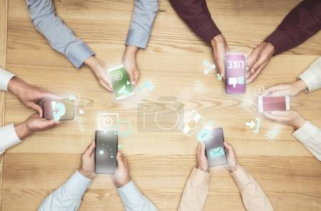 Photo for Top view of businesspeople on meeting using social media on smartphones on wooden tabletop - Royalty Free Image