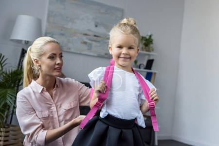 mother preparing daughter to school