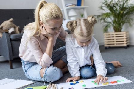 Photo pour Jeune mère avec mignonne petite fille apprenant des chiffres tout en étant assis sur le sol à la maison - image libre de droit