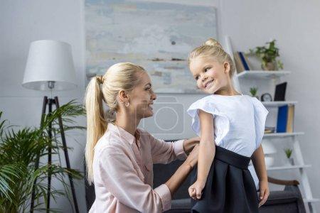 Mother dressing daughter to school