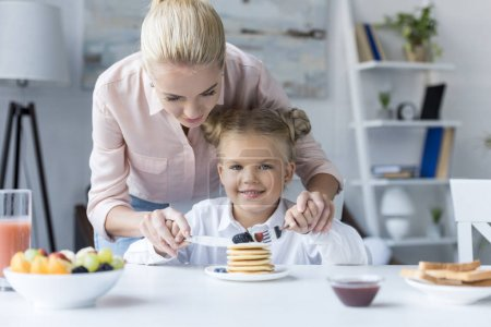 mother and daughter eating pancakes