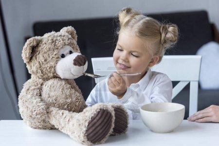 child feeding teddy bear