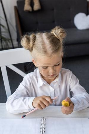 Photo for Adorable little girl sharpening pencil while preparing for school - Royalty Free Image