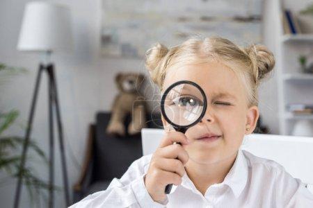 Photo pour Adorable petite fille tenant loupe et regardant la caméra - image libre de droit
