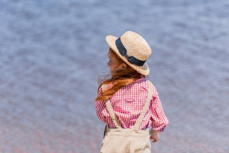 Child in straw hat at seashore