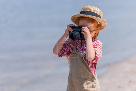 Photo for Cute little redhead girl photographing with camera at seashore - Royalty Free Image