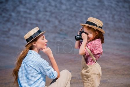 child photographing mother near sea