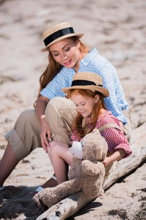 mother and daughter with teddy bear on beach