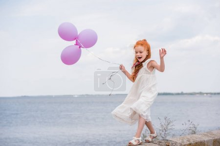 child with balloons on quay