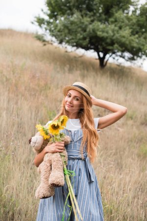 Girl with teddy bear and sunflowers