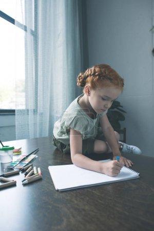 Photo pour Belle petite fille, tout en étant assis sur la table de dessin - image libre de droit