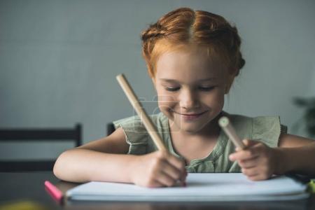 Photo pour Heureuse belle petite fille dessin aux crayons de couleur - image libre de droit