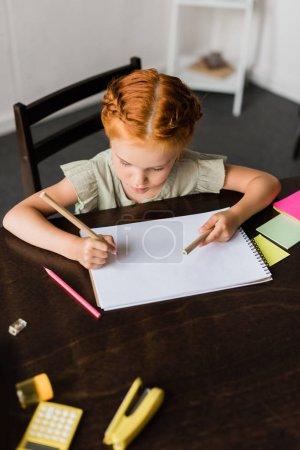 Photo pour Vue de dessus de belle petite fille dessin dans album - image libre de droit