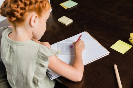 Photo pour Belle rouquine petite fille dessin dans album - image libre de droit