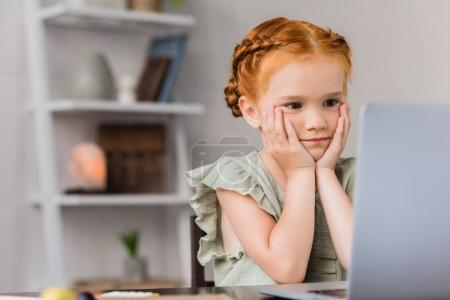 little girl looking at laptop