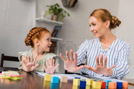 Photo pour Heureuse mère et apprentissage des mathématiques fille avec les doigts à la maison - image libre de droit