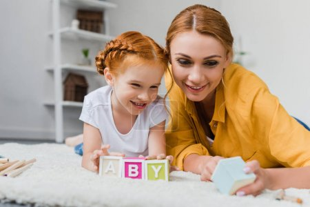 mother and daughter playing with letter cubes