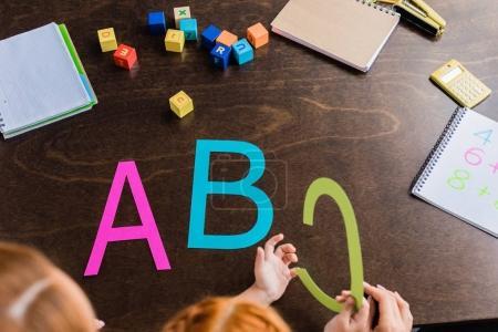 Photo pour Plan recadré de mère et fille apprenant alphabet - image libre de droit