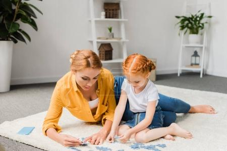mother and daughter assembling puzzle