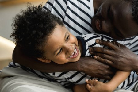 Photo for Cropped shot of happy african american father and son hugging and having fun together - Royalty Free Image