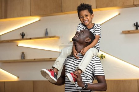 Photo for Happy african american father carrying cute little son on neck indoors - Royalty Free Image