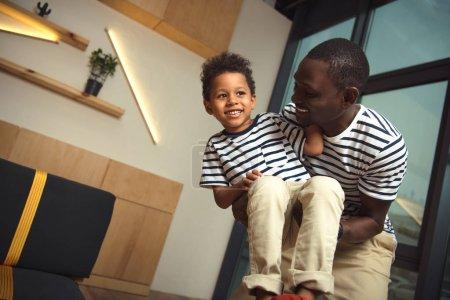 Photo pour Heureux père afro-américain portant peu de fils et de s'amuser au café - image libre de droit