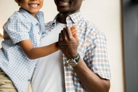 Photo pour Recadrée tir d'heureux père afro-américain, transportant des fils sourire mignon - image libre de droit