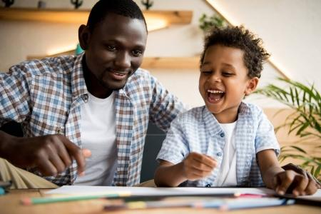 Photo for Happy african american father and son laughing while drawing together in cafe - Royalty Free Image