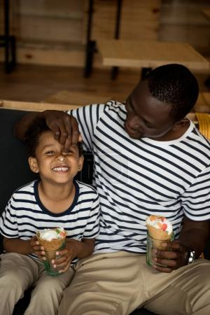 Photo for Happy african american father and son eating ice cream and having fun in cafe - Royalty Free Image