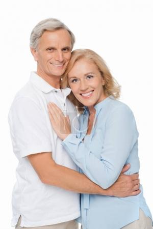 Photo for Smiling senior couple embracing and looking at camera isolated on white - Royalty Free Image