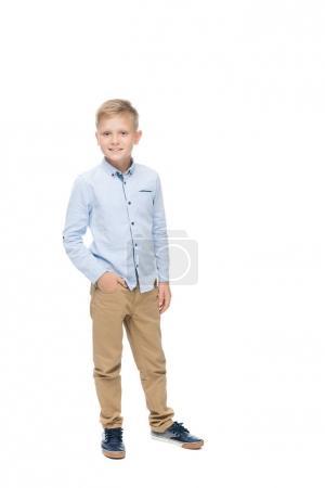 Photo pour Petit garçon caucasien souriant avec la main dans la poche regardant la caméra isolée sur blanc - image libre de droit