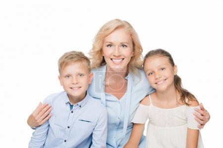 Foto de Retrato de mujer feliz abrazando a nietos y mirando a cámara aislada en blanco - Imagen libre de derechos