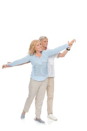 Photo pour Beau couple mature heureuse tenant par la main et à la recherche de loin isolé sur blanc - image libre de droit