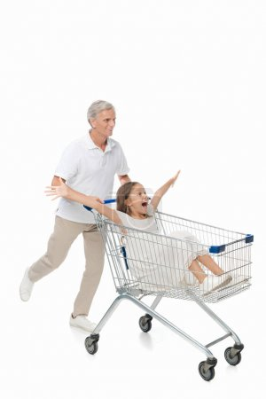 Grandfather riding granddaughter in shopping cart