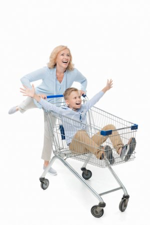 Mother riding son in shopping cart