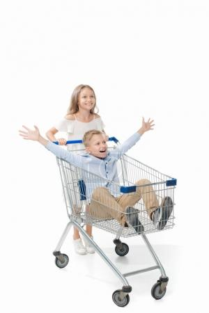 Sister riding brother in shopping cart